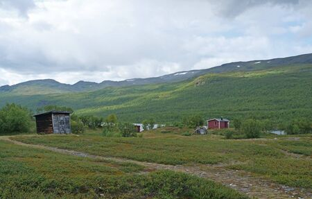 Sami houses in green hills landscape of Abisko National Park. Goahti is Lappish traditional dwelling made from fabric, peat moss and timber. Lapland, Northern Sweden on Kungsleden trail. Summer sunny day.