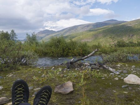 hiking boots with view on wild river with birch tree forest and mountains in golden light. Lapland nature landscape in summer, moody sky