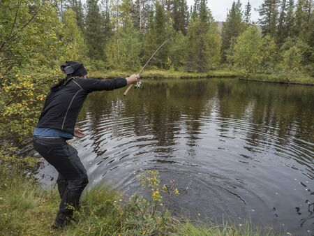 Pêcheur pêcheur homme pêcher la truite dans un petit lac en Suède Laponie Banque d'images