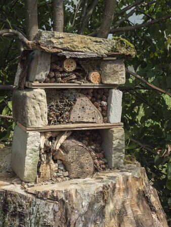 Home made insect hotel decorative bug house from sandstone and wood, ladybird and bee home for butterfly hibernation and ecological gardening. Protection for insects concept Reklamní fotografie