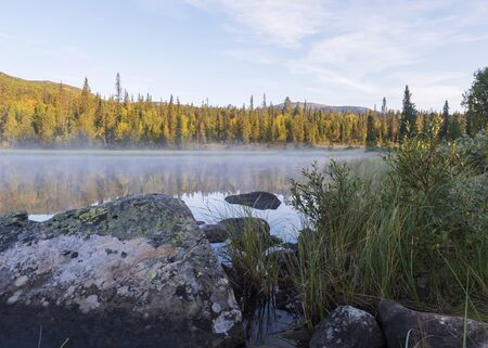 Beautiful morning sunrise over lake Sjabatjakjaure with haze mist in Sweden Lapland nature. Mountains, birch trees, spruce forest, rock boulders and grass. Sky, clouds and clear water