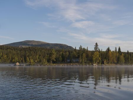 Beautiful morning over lake Sjabatjakjaure with view on Parte Fjallstuga STF mountain cabin, green hills and birch trees. Sweden Lapland at the Kungsleden Trail.