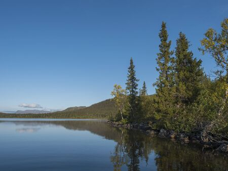 Beautiful morning over lake Sjabatjakjaure in Sweden Lapland nature. Mountains, birch trees, spruce forest, rock boulders and grass. Sky, clouds and clear water