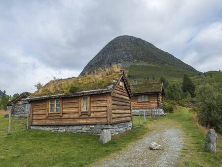 Traditional Scandinavian wooden cabins sod or turf roof house at a campsite in the Reinheim national Park. View from scenic road 63, Norway