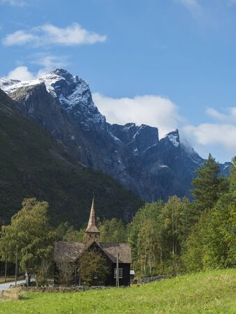 Kors Church, old wooden parish church in Rauma in Romsdal valley, Norway with road E136, green forest and mountain massif Trolltindene, Troll wall Trollveggen. Summer blue sky white clouds