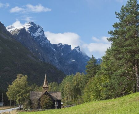 Kors Church, old wooden parish church in Rauma in Romsdal valley, Norway with road E136, green forest and mountain massif Trolltindene, Troll wall Trollveggen. Summer blue sky white clouds.
