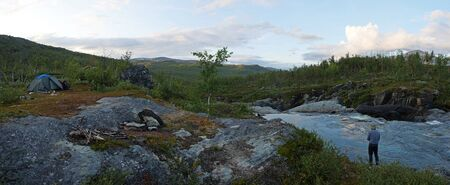 Wide panoramic Lapland landscape with with angler fisherman and small tent and rapids of river Kamajakka, rock, birch trees and mountains at Rovvidievva sami village, Northern Sweden, Summer evening Reklamní fotografie