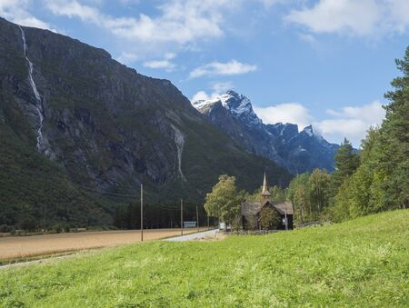 Kors Church, old wooden parish church in Rauma in Romsdal valley, Norway with road E136, green forest and mountain massif Trolltindene, Troll wall Trollveggen. Summer blue sky white clouds. Stock fotó