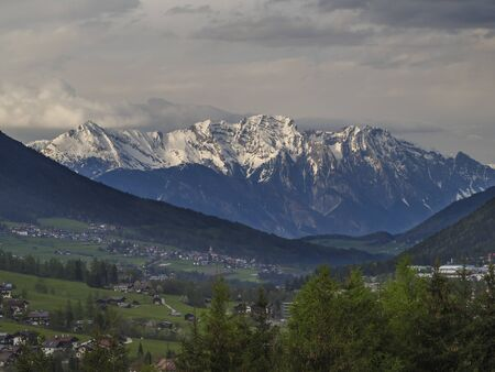 Spring mountain rural landscape. View over Stubaital Stubai Valley near Innsbruck, Austria with village Neder, green meadow, forest, snow covered alpen mountain peaks, evening dramatic clouds and light