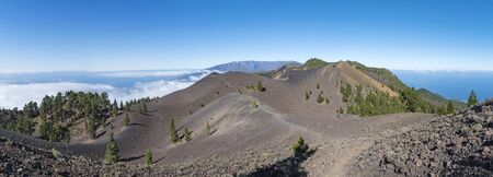 Panoramatic view of volcanic landscape with lush green pine trees, colorful volcanoes and white clouds at path Ruta de los Volcanes, hiking trail. La Palma, Canary Islands, Spain, Blue sky background.