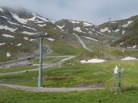 View on snow spotted mountain slopes at Mittelstation with Stubaier Gletscher gondola lift at Stubai Glacier in Tyrol, Austria and grazing sheep and cows, Summer