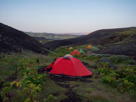 Colorful tents in Botnar campsite at Iceland on Laugavegur hiking trail, green valley in volcanic landscape among lava fields with view on Myrdalsjokull glacier. Early morning sunrise view