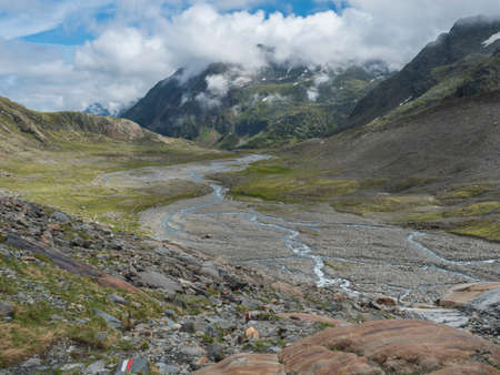 Summer view of alpine mountain valley with winding stream and glacial lake, Sulzenauferner Glacier, Stubai Alps, Austria
