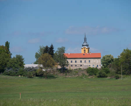 spring landscape with lush green grass meadow, fresh deciduous tree with big stone house and country baroque church tower in luzicke hory, Lusatian Mountains, blue sky Zdjęcie Seryjne