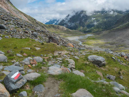 Summer view of alpine mountain valley with Stubai hiking trail, Stubai Hohenweg, rock, boulders and river stream. Tyrol Alps, Austria