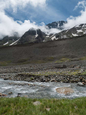 Summer view of alpine landscape with snow-capped mountain peaks and wild river stream. Tyrol, Stubai Alps, Austria