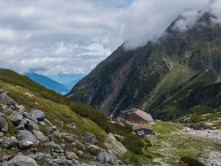 Summer view of Sulzenau mountain hut, Sulzenauhutte with resting tourist people. Alpine in mountain valley in Stubai Austrian Alps