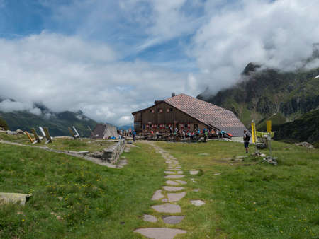 Stubai Valley, Innsbruck-Land, Tyrol, Austria, July 4, 2020: Sulzenau mountain hut, Sulzenauhutte with resting tourist people. Summer sunny day, mountain valley in Austrian Alps Publikacyjne