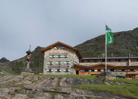 Stubai Valley, Innsbruck-Land, Tyrol, Austria, July 4, 2020: View of Dresdner Huette alpine hut, mountain hotel, summer foggy morning, light sky background