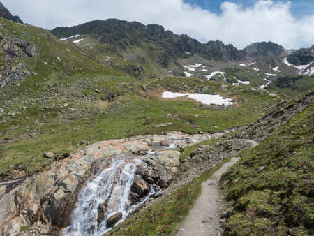Summer view of Stubai hiking trail with with snow-capped mountain peak, waterfall cascade ofFreigerbach stream, rocks, green meadow and blooming alpenrose, Tyrol, Stubai Alps, Austria Zdjęcie Seryjne