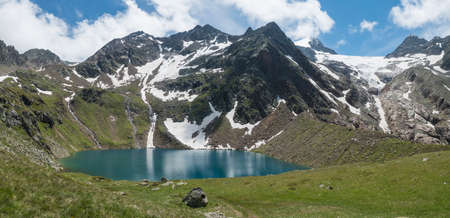 Panoramic view of turquoise blue mountain lake Grunausee in alpine landscape with green meadow and snow-capped mountain peaks. Tyrol, Stubai Alps, Austria, summer sunny day