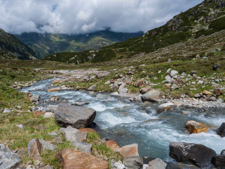 Summer view of alpine landscape with snow-capped mountain peaks and wild Freigerbach stream. Tyrol, Stubai Alps, Austria