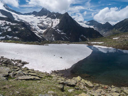 Beautiful glacial lake with springs from melting ice glacier with sharp snow-capped mountain peaks reflecting on water surface. Tyrol, Stubai Alps, Austria, summer sunny day Zdjęcie Seryjne