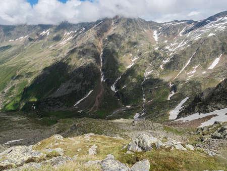 view from Niederl saddle on Nurnberger Hutte mountain hut and snow-capped peaks at Stubai hiking trail, Stubai Hohenweg, Summer rocky alpine landscape of Tyrol, Stubai Alps, Austria