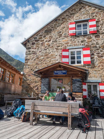 Stubai Valley, Innsbruck-Land, Tyrol, Austria, July 4, 2020: hiker people resting at terrace of Nuernberger Huette, an alpine mountian hut at sunny summer day