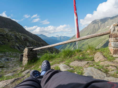 hikers legs, foot in rubber clogs relaxing at view from Nurnberger Hutte hut, valley with mountain peaks at Stubai hiking trail, Summer, Tyrol, Stubai Alps, Austria Zdjęcie Seryjne