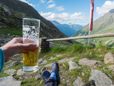 hiker holding beer glass with foot in rubber clogs relaxing at view from Nurnberger Hutte hut, valley with mountain peaks at Stubai hiking trail, Summer, Tyrol, Stubai Alps, Austria