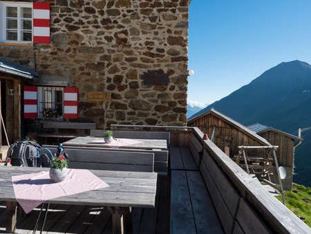 empty terrace of Nurnberger Hutte mountain hut at valley with sharp mountain peaks at Stubai hiking trail, Stubai Hohenweg, Summer rocky alpine landscape of Tyrol, Stubai Alps, Austria. Zdjęcie Seryjne