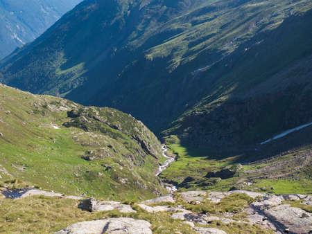 Green mountain valley with spring at Stubai hiking trail, Stubai Hohenweg, Summer rocky alpine landscape of Tyrol, Stubai Alps, Austria