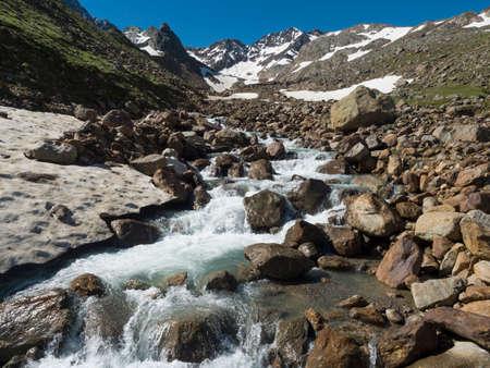 View of wild spring stream at green alpine mountain valley at Stubai hiking trail, Stubai Hohenweg, Summer rocky landscape of Tyrol, Stubai Alps, Austria