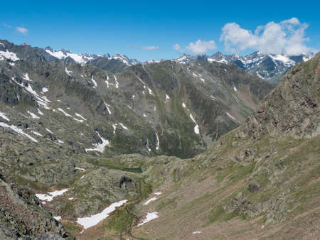 view of mountain valley with winding stream of spring and snow-capped peaks at Stubai hiking trail, Stubai Hohenweg, Summer rocky alpine landscape of Tyrol, Stubai Alps, Austria