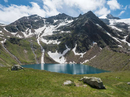 Beautiful turquoise blue mountain lake Grunausee in alpine landscape with green meadow and snow-capped mountain peaks. Tyrol, Stubai Alps, Austria, summer sunny day