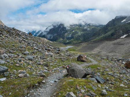 Summer view of alpine mountain valley with Stubai hiking trail, Stubai Hohenweg, rock, boulders and river stream. Tyrol Alps, Austria