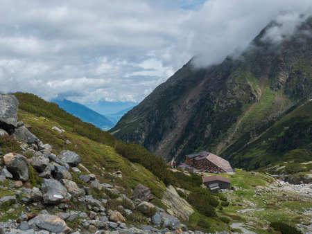 Summer view of Sulzenau mountain hut, Sulzenauhutte with resting tourist people. Alpine in mountain valley in Stubai Austrian Alps