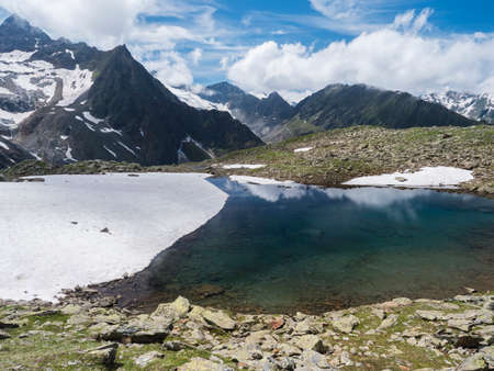 Beautiful glacial lake with springs from melting ice glacier with sharp snow-capped mountain peaks reflecting on water surface. Tyrol, Stubai Alps, Austria, summer sunny day Archivio Fotografico