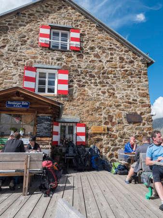Stubai Valley, Innsbruck-Land, Tyrol, Austria, July 4, 2020: hiker people resting at terrace of Nuernberger Huette, an alpine mountian hut at sunny summer day