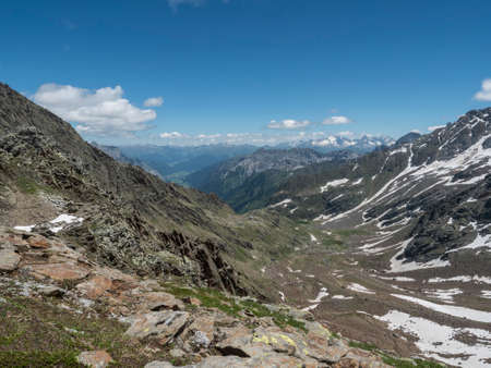view of mountain valley and snow-capped peaks at Stubai hiking trail, Stubai Hohenweg with Bremer hutte. Summer rocky alpine landscape of Tyrol, Stubai Alps, Austria