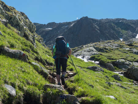 Lonely man hiker with heavy backpack at Stubai hiking trail, Stubai Hohenweg at green summer alpine mountain valley with spring stream. Tyrol, Austrian Alps