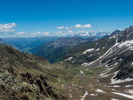 view from Simmingjochl mountain saddle on sharp snow-capped peaks at Stubai hiking trail, Stubai Hohenweg, Alpine landscape of Tyrol, Stubai Alps, Austria. Summer blue sky