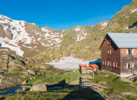 Stubai Valley, Innsbruck-Land, Tyrol, Austria, July 5, 2020: Early morning view of Bremer Hutte, alpine mountian wooden hut with blue lake from melting snow tongues, moutain peaks, sunny summer day. Editoriali