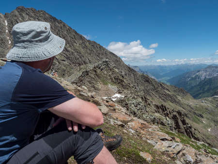 Man hiker looking at mountain valley and snow-capped peaks at Stubai hiking trail, Stubai Hohenweg with Bremer hutte. Summer rocky alpine landscape of Tyrol, Stubai Alps, Austria