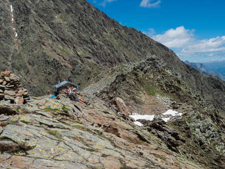 Stubai Valley, Innsbruck-Land, Tyrol, Austria, July 5, 2020: Couple of middle age hikers have a rest and enjoying view at shelter at Simmingjochl mountain saddle at Stubai hiking trail, Hohenweg
