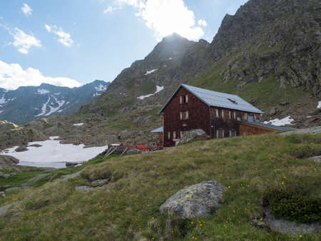 Stubai Valley, Innsbruck-Land, Tyrol, Austria, July 5, 2020: View of Bremer Hutte, an alpine mountian wooden hut with blue lake from melting snow tongues, moutain peaks, sunny summer day.