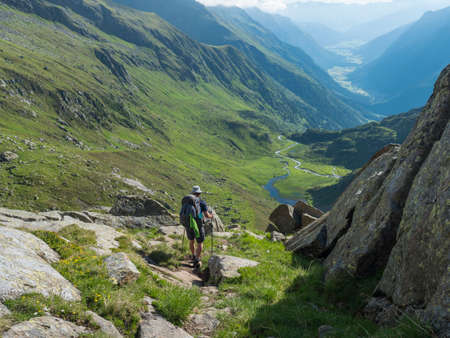 Lonely man hiker with heavy backpack at Stubai hiking trail, Stubai Hohenweg at green summer alpine mountain valley with winding river spring stream. Tyrol, Austrian Alps