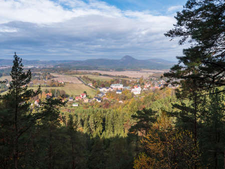View from Hrabencina vyhlidka lookout on village Sloup v cechach in luzicke hory, Lusatian Mountains with autumn colored deciduous and coniferous tree forest and green hills, blue sky, white clouds Archivio Fotografico