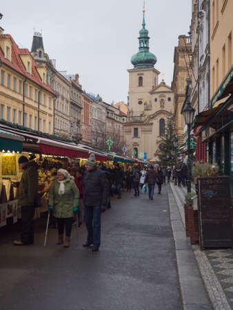 Prague, Czech Republic, December 12, 2019: Tourist people shopping at traditional christmas Market, Havelska trznice street with stalls selling gifts, souvenirs, christmas decorations,toys and fruits. Editoriali